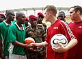US Navy 080201-N-0577G-073 Lt. j.g. Phillip McCorvey and a member of the local Equatorial Guinea soccer team exchange soccer balls signed by the members of each team.jpg