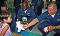 US Navy 080710-N-0096V-038 Chief Boatswain's Mate Ernest Pippin and Boatswain's Mate 2nd Class Carlos Gonzales, assigned to the amphibious dock landing ship USS Tortuga (LSD 46), give a child a doll.jpg