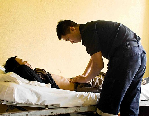US Navy 090715-N-9689V-008 Republic of Singapore Navy Maj. Boon Hor Ho examines a local man suffering from abdominal pain during a Pacific Partnership 2009 medical civic action project at Niu'ui Hospital