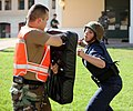 US Navy 090717-N-1442D-001 Postal Clerk Seaman Carrie Rymer demonstrates her knowledge of non-lethal security techniques to Master-at-Arms 1st class Alexis Repollet during training in order to qualify to become a member of the.jpg