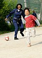 US Navy 100502-N-0864H-232 Chief Yeoman Roszetta Dean plays kickball with a child at the Kodomono-ie Children's Home.jpg