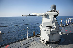 US Navy 111231-N-KS651-967 A Mk 38 MOD 2 25mm machine gun system aboard the amphibious dock landing ship USS Pearl Harbor (LSD 52) ejects casings d.jpg