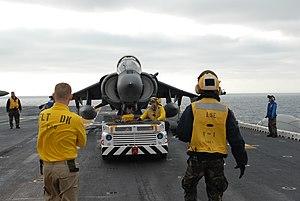 US Navy 120202-N-VG904-016 Aviation Boatswain's Mate (Handling) 3rd Class Wesley Alcock, from Littleton, Colo., maneuvers an AV-8B Harrier on the f.jpg