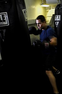 US Navy 120213-N-UT411-221 Airman Tanner Schaffer, assigned to Strike Fighter Squadron (VFA) 81, boxes in the sweat box gym aboard the Nimitz-class.jpg