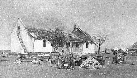 Boer civilians watching British soldiers blow up their house with dynamite: Boers were given 10 minutes to gather belongings VerskroeideAarde1 crop.jpg