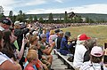 Visitors watching Old Faithful Geyser erupting. Old Faithful Inn in background 5640 (14618307008).jpg