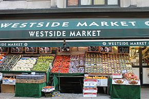 several shelves of produce displayed outside of a grocery store on the Upper West Side