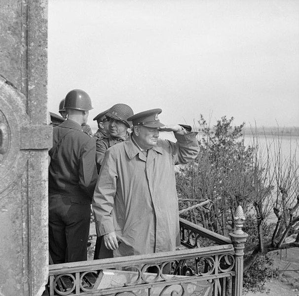Winston Churchill with American generals on a balcony watching Allied vehicles crossing the Rhine.