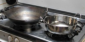 Karahi - A wok sits next to a karahi on a Western-style stove. Note that the flat-bottomed karahi (right) sits on an ordinary burner cover, while the round-bottomed wok balances in a wok-ring. Karahi often have round (loop-shaped) handles.