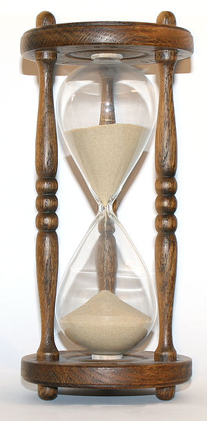 The flow of sand in an hourglass can be used to measure the passage of time. It also concretely represents the present as being between the past and the future. Wooden hourglass 3.jpg