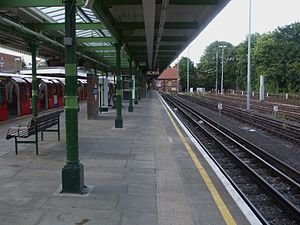 Woodford tube station - Bay platform looking north towards buffers, used by eastbound terminating trains from Central London. A westbound Central line train stands on the westbound platform on the left.