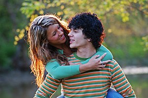 A young woman and man embracing while outdoors.
