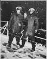 """Two Coast Guard officers brave the wintry blasts of snow aboard a Coast Guard cutter on the North Atlantic patrol. The - NARA - 513211.tif"