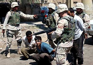 Iraq War in Anbar Province - American soldiers with the 115th Military Police Company searching Iraqis at a vehicle checkpoint in Fallujah in July 2003