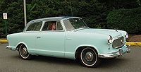 A traditional two-door sedan, 1959 Rambler American with a B-pillar and fixed window frames.