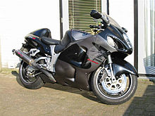 A modern sport motorcycle with enclosed black and gray bodywork leaning on its sidestand on smooth paving stones in front of a white wall.
