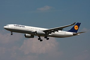 A white, blue, yellow and grey Lufthansa A330 on approach, configured for landing with gears down and flaps extended