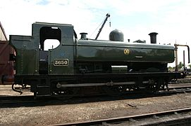 "A pannier tank locomotive is standing outside an engine shed. The locomotive is mainly painted green above the running plate, although the chimney is black. On the side of the pannier tank a yellow circle encloses the yellow letters ""G W R"". The G and R are shaped to match the curve of the enclosing circle."