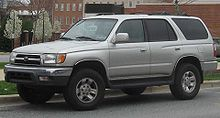 A light gray sport-utility vehicle parked on a street with brick buildings in the background, facing left