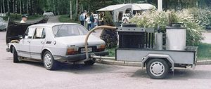 Wood gas generator - Saab 99 running on wood gas in Finland. The gas generator is on the trailer.