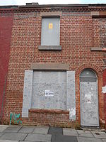 A colour photo of a red-bricked house with boarded up windows and doors
