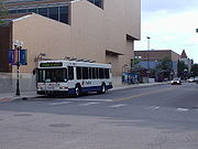 An AATA bus, with the blue-roofed Blake Transit Center in the background.