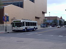 A white low-floor city bus on an empty city street