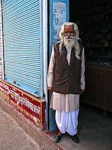Vieil homme à Rishikesh sur le pas de sa boutique, portant le costume traditionnel: pantalon dhotî blanc, veste achkan brune sur kurta de coton beige saumon à patte boutonnée