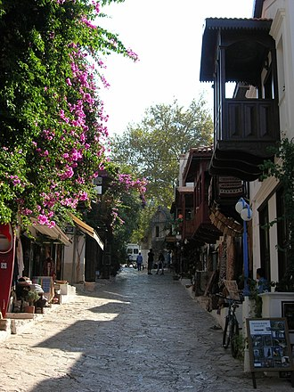 Kaş - A street in Kaş with traditional houses and a Lycian tomb in the background