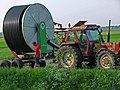 A tractor with a huge turning mobile role of flexible water pipe to spray the fields in Drenthe, 2012.jpg