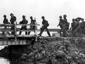 Agat, Guam - Marines cross a bridge in Agat during the liberation of Guam in 1944.