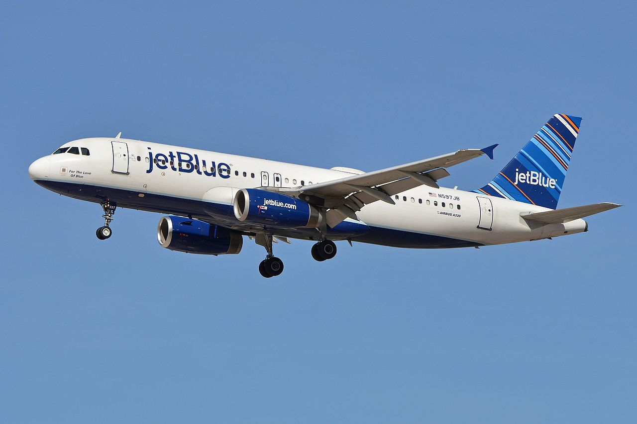 """A white plane with the word """"jetBlue"""" painted in the front and a blue tailfin on the back prepares to land as its landing gear is deployed"""