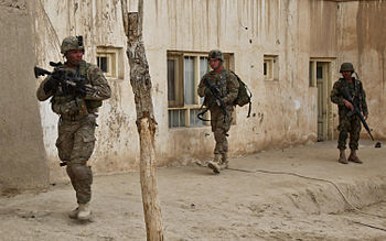 U.S. and Afghan National Army soldiers move to...
