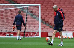 Arsène Wenger kicking a football during an Arsenal training session