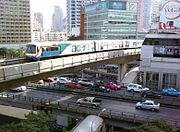 """An elevated train, painted in blue, white and a red stripe and with advertisements with the name """"acer"""", running above a road lined with many tall buildings and crossing an intersection with a flyover bridge with many cars"""