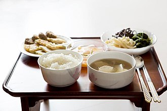 Namul - A single person bapsang (meal table) with bap (cooked rice), guk (soup), kimchi, pyeonyuk (meat slices), and three namul banchans (spinach namul, brakenfern namul, and balloon flower root namul)