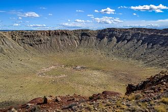 Meteor Crater - Looking into the crater from the north rim. The rust colored area on the far (south) rim is where the last mining for the meteorite occurred in 1929 and was believed to be the site of the bulk of the meteorite. Rock around the south rim is uplifted.