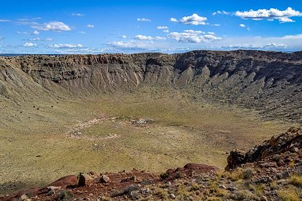Looking into the crater from the north rim. The rust colored area on the far (south) rim is where the last mining for the meteorite occurred in 1929 and was believed to be the site of the bulk of the meteorite. Rock around the south rim is uplifted. Barringer-1001.jpg