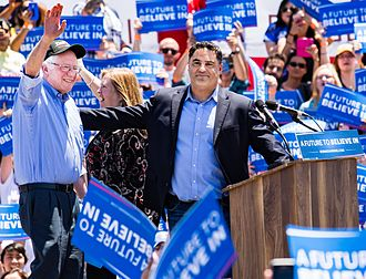 Cenk Uygur - Uygur with Bernie Sanders at a campaign rally.