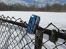 "Aluminum can marked ""Bud Light"" in wedged into chain-link fence in front of snow-covered field"