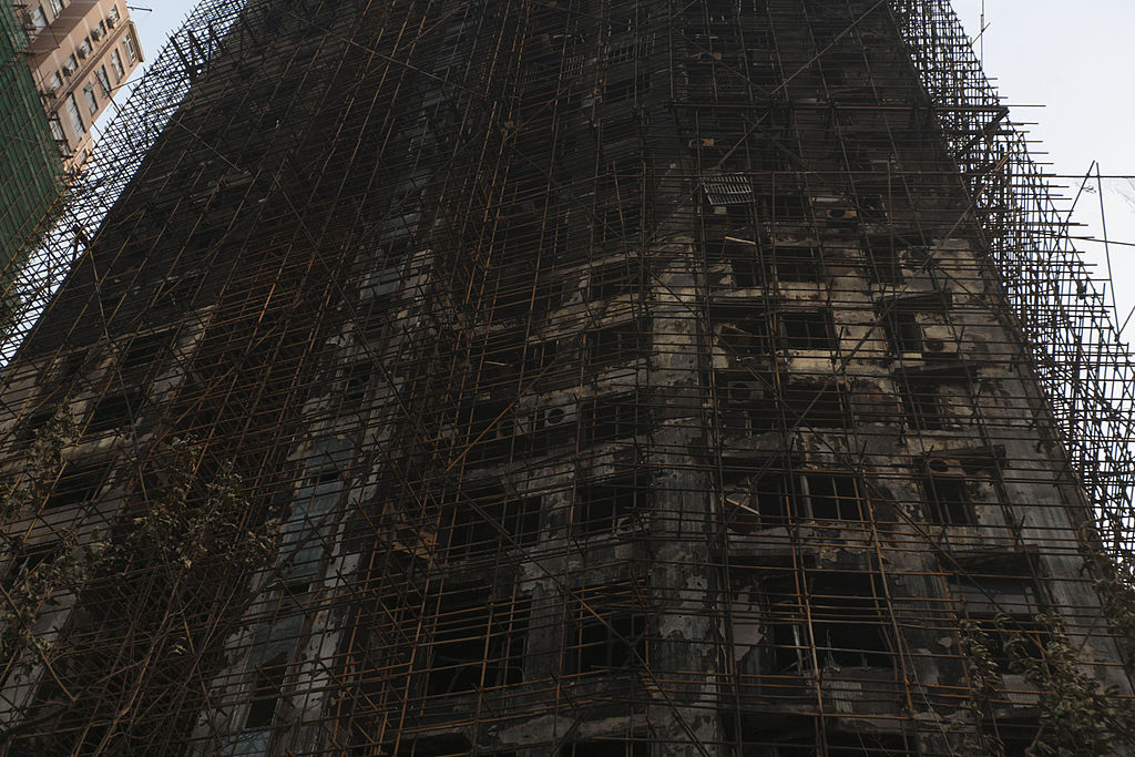 An upward view of a burned-out high-rise: a blackened mess of tangled scaffolding and holes for windows.