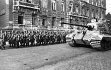 A large tank with sloped frontal armour and a flat faced turret, by a column of marching soldiers wearing overcoats and helmets, in a wide city street. A large building to the rear shows the scars of battle.