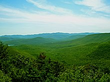A color photograph of green mountains under a blue sky.