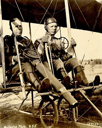Aeronautical Division, U.S. Signal Corps - Captain Charles Chandler (with prototype Lewis Gun) and Lt. Roy Kirtland in a Wright Model B Flyer after the first successful firing of a machine-gun from an aeroplane on June 7, 1912.