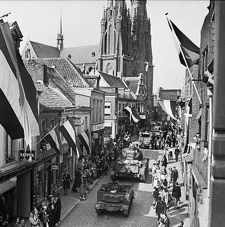 People of Eindhoven (during World War II) watching Allied forces entering the city following its liberation from Axis forces on 19 September 1944. Cheering crowds line the streets as Cromwell tanks of 2nd Welsh Guards enter Eindhoven in Holland, 19 September 1944. BU945.jpg
