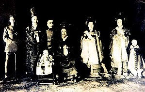 This photo, taken about 1915 (is actually a compilation of individual photographs taken since the Japanese did not allow them to all be in the same room at the same time, and some were forced to leave Korea), shows the following royal family members, from left: Prince Uichin, the sixth son of Gojong; King Sunjong, the second son and the last monarch of Joseon; Prince Yeongchin, the seventh son; then former King Gojong; Queen Yundaebi, wife of Sunjong; Deogindang Gimbi, wife of Uichin; and Yi Geon, the eldest son of Uichin. The seated child in the front row is Princess Deokhye, Gojong's last child.)