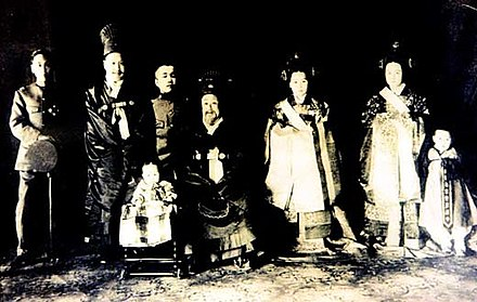 This compilation photo, taken about 1915, shows the following royal family members, from left: Prince Ui (Ui chinwang yicinwang), the 6th son of Gojong; Sunjong, the 2nd son and the last monarch of Joseon; Prince Yeong (Yeong chinwang yeongcinwang), the 7th son; Gojong, the former King; Queen Yoon (Yoon daebi), Queen Consort of Sunjong; Deogindang Gimbi, wife of Prince Ui; and Yi Geon, the eldest son of Prince Ui. The seated child in the front row is Princess Deokhye (Deokhye ongju deoghyeongju), Gojong's last child. (This is a compilation of individual photographs since the Imperial Japanese did not allow them to be in the same room at the same time, and some were forced to leave Korea.) Choseon Imperial family.jpg