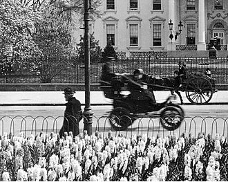 """History of the electric vehicle - Columbia Electric's (1896-99) """"Victoria"""" electric cab on Pennsylvania Ave., Washington D.C., seen from Lafayette Park in 1905."""