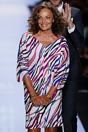 A woman with wavy and curly hair wearing a white dress with multi-colored stripes smiles on a fashion runway