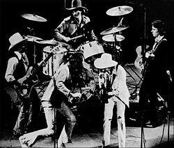 A group of men performing on a stage. One is playing a violin, three are playing guitars, and one is playing drums. The drummer and two of the guitarists are wearing cowboy hats.